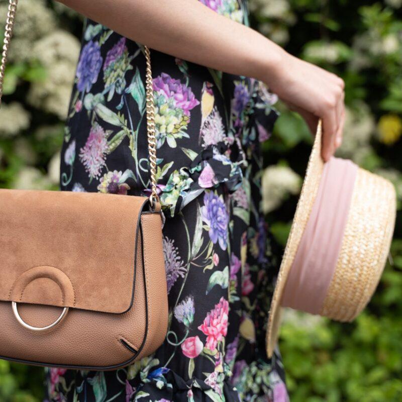 Dame går med en dametaske og hat